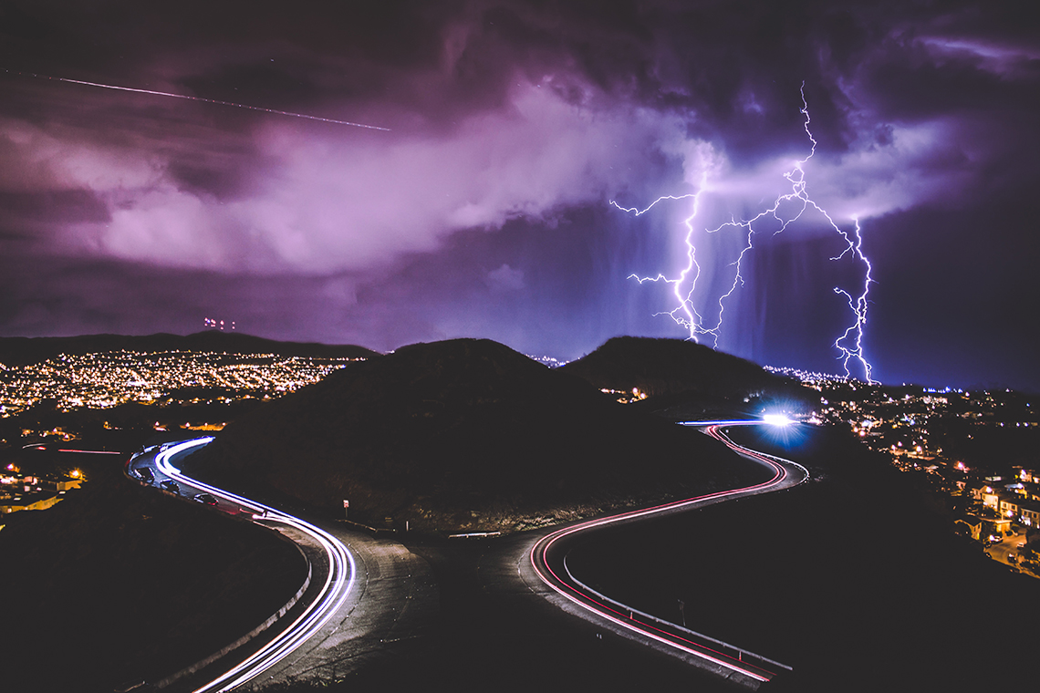 lightening strking in background of highway