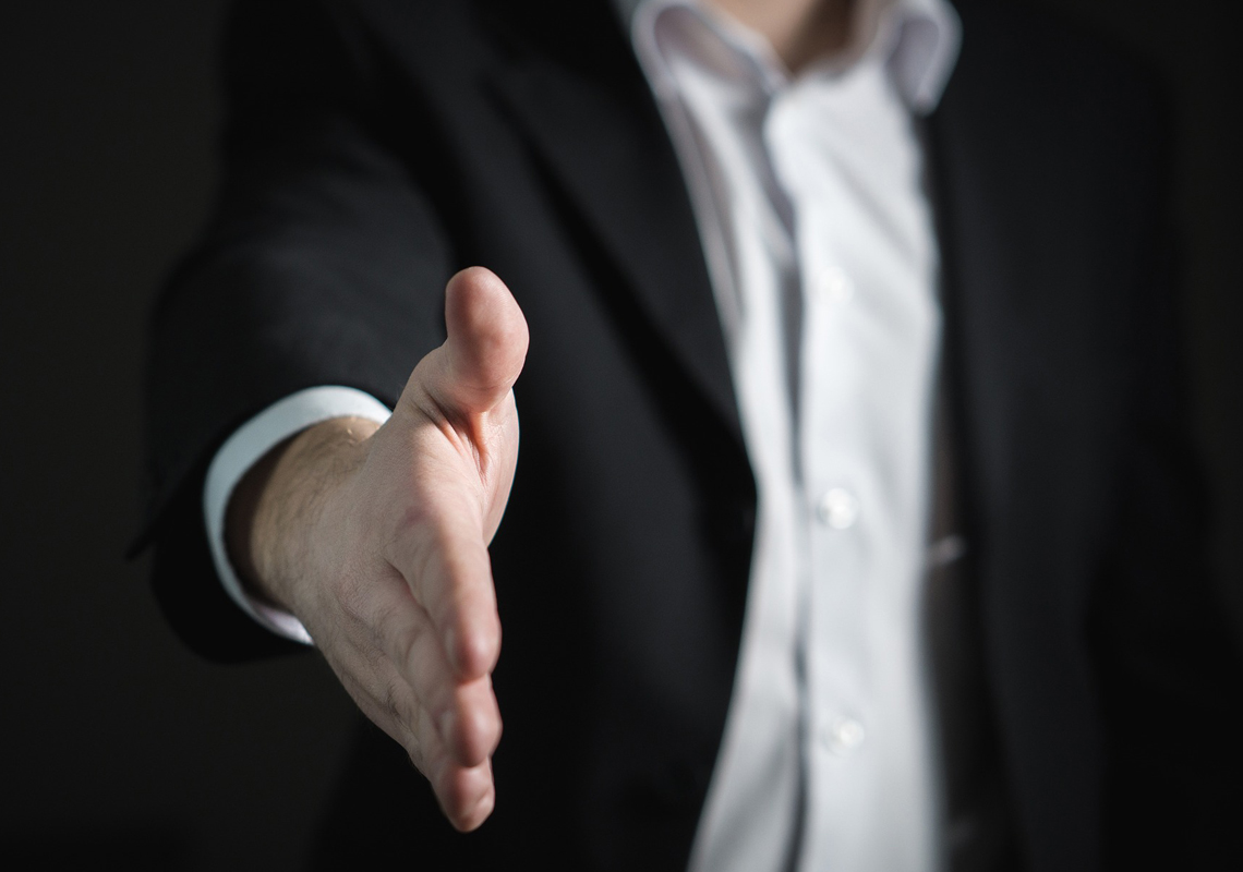 man holding arm out ready to shake hands