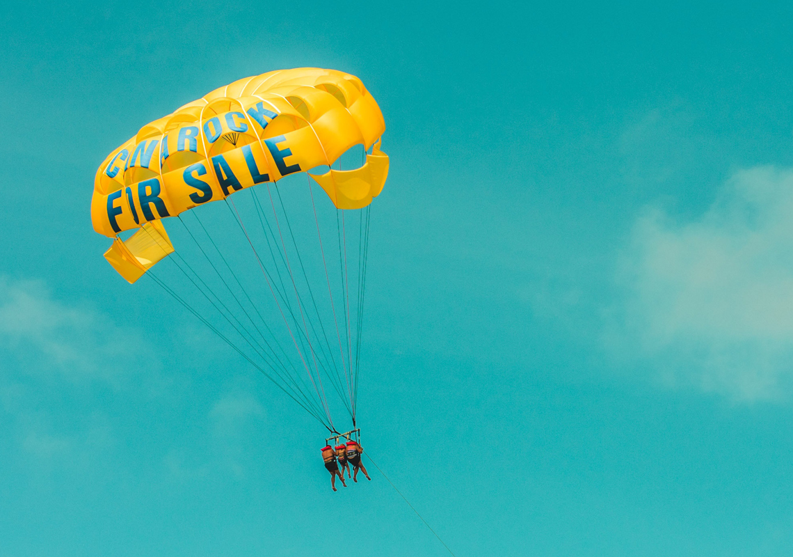 couple floating in a parachute with for sale written on