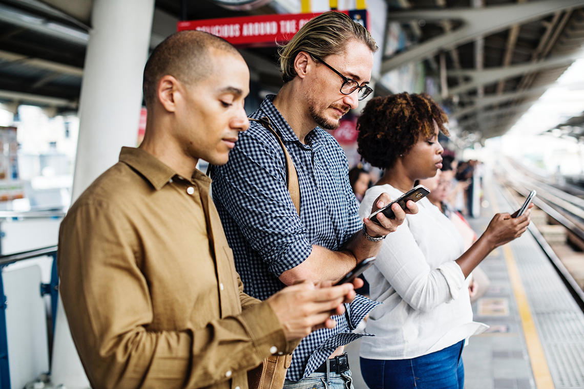 3 people waiting for train looking at their phones viewing accelerated mobile pages