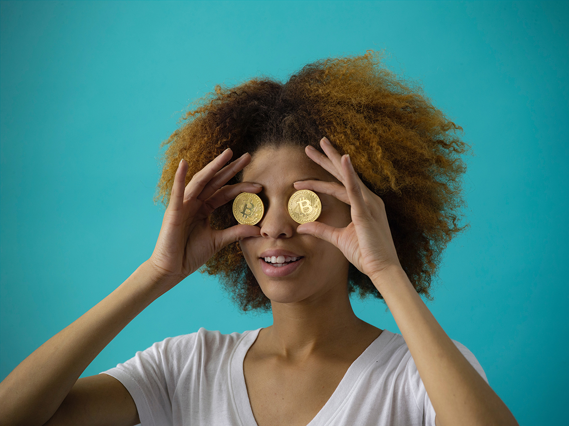 woman holding bitcoin to her eyes looking at wordpress themes