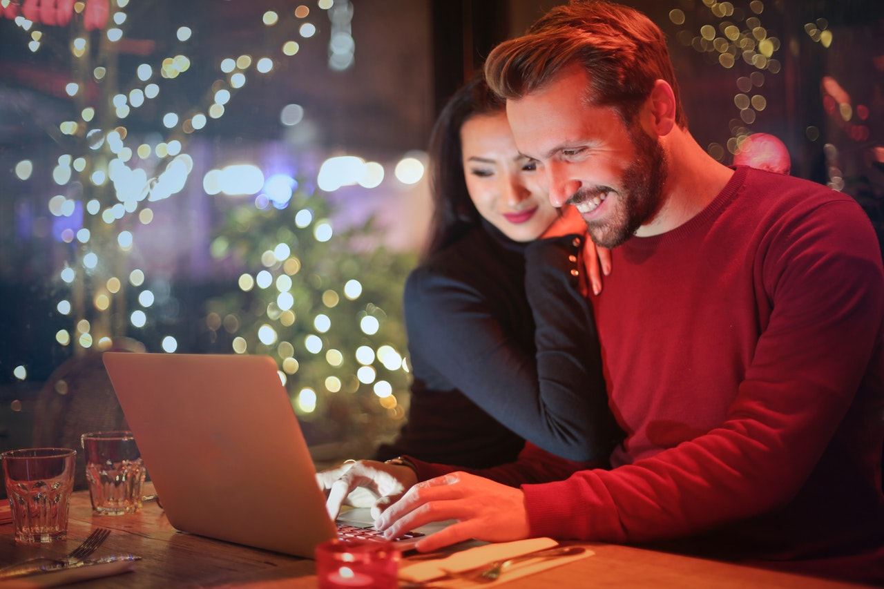 couple in bar booking appointment via a wordpress plugin on a laptop